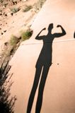 Strength in Shadow. A young woman shows off her strength in the desert sun Royalty Free Stock Photos