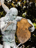 The strength of the shield. A strange green statue with appearances by older man with his right hand continued open and the left holding a shield, the shield can Royalty Free Stock Photo