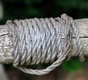 Strength in Strands. Tree trunk serves as old water well bar. Aging rope is twisted around tree trunk. Rope strands for orderly rows Royalty Free Stock Image