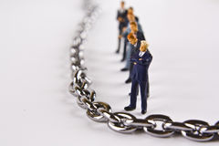 Strength in the Team. Miniature businessmen standing in line next to a chain Royalty Free Stock Photography