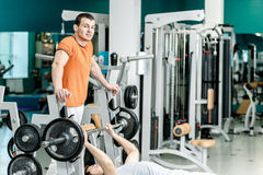 Strength training in the gym. Two young men are engaged in sport Stock Photography