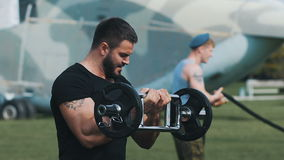 Strength training at a military base. Muscular man raises the bar with the weight. Around military equipment stock video