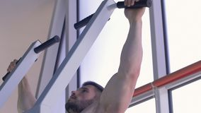 Strength training, muscular bodybuilder man with beautiful sports body pulls up on simulator during power workout at stock video