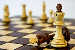 Strength through unity. White chess pieces overcoming black king Stock Photography
