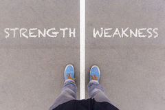 Strength and weakness text on asphalt ground, feet and shoes on Royalty Free Stock Photography