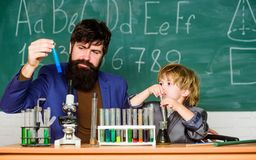 Strength On Your Side. Little kid learning chemistry in school laboratory. teacher man with little boy. father and son royalty free stock photo