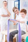 Strengthening the arm muscles with the band. Little cute boy strengthening arm muscles with elastic band during physical therapy in rehabilitation clinic royalty free stock images