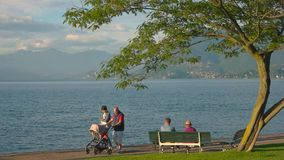 People near lake Maggiore, summer. 20.06.2016 - Stresa, Italy. People near lake Maggiore, summer. Couple with baby carriage seniors How time flies stock footage