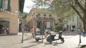Town street, sunny day. 20.06.2016 - Stresa, Italy Town street sunny day Parked vintage scooters stock video footage