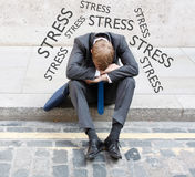 Stress. A business man with stress sitting on the street Stock Photography