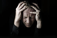 Stress. SELF PORTRAIT - Male Holding Head in hands with stressful look Royalty Free Stock Image