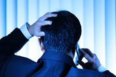 Stress. A stressed businessman talking on the phone (in blue tone stock photo