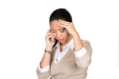 Stress and anxiety. A businesswoman feeling despair as she listens to the news over the mobile phone, isolated on white Stock Photo