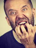 Man biting his nails. Stress, anxiety, emotions and problems concept. Scared, stressed man biting his nails stock photography