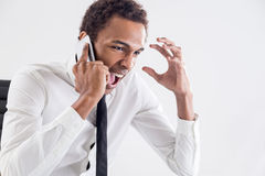 Stress and authority abuse concept. Furious african american businessman shouting at interlocutor over the phone. Concept of stress and authority abuse Royalty Free Stock Photos