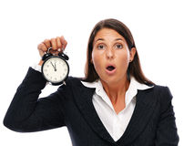 Stress - business woman is late. Business woman holding a clock that shows 5 to 12. Concept for stress or getting late. Isolated on a white background Royalty Free Stock Photography