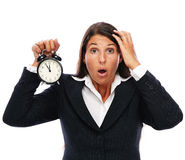 Stress - business woman is late. Business woman holding a clock that shows 5 to 12. Concept for stress or getting late. Isolated on a white background Royalty Free Stock Images