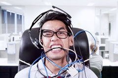 Stress businessman biting cables at office. Stressful businessman with headset biting cables at office Stock Image