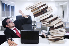 Stress businessman and falling books at office. With PC and laptop Stock Photo