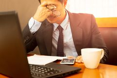 Stress businessman holding eyeglasses rubbing his eyes after long working hours. royalty free stock photography
