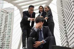 Stress Businessman and laughing coworkers. Depress sad Businessman sit on footpath of modern city while other Business coworkers laugh at him. Head down with Royalty Free Stock Image