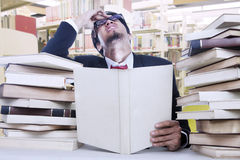 Stress businessman and stack of books Stock Photos