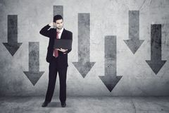 Stress businessman standing with downward arrows Stock Image