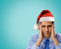 Stress in christmas. Portrait of stressed man wearing red santa hat looking angry and distressed with copyspace on blue background Stock Photos