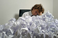 Stress concept. Young businessman next to stack of crumpled paper Royalty Free Stock Image