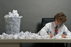 Stress concept. Young businessman next to stack of crumpled paper Stock Photography