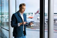 Businessman using tablet computer in airport stock photography
