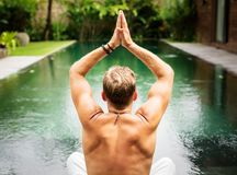 Man practice yoga by the pool. Stress free man practice yoga by the pool Royalty Free Stock Photo