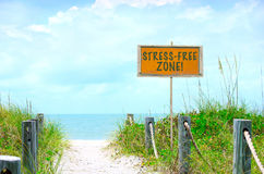 STRESS-FREE ZONE sign at beautiful beach path to ocean. STRESS-FREE ZONE sign at beautiful beach with sandy path down to the calm blue ocean water with soft Royalty Free Stock Photography