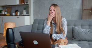 Stress and frustration. Young beautiful blonde business woman gets upset, struggles using laptop working from home.