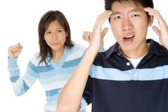 Stress Headache. A man has a headache from relationship stress (woman slightly off-focus behind Stock Photo