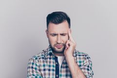 Stress and health care concept. Close up portrait of attractive. Guy with bristle, stubble having a headache, with close eyes touching his temple while standing Stock Image