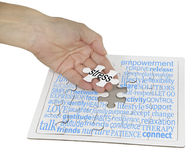 Stress Management Puzzle Word Cloud. A hand holding the final jigsaw piece over a jigsaw puzzle showing a word cloud containing words relevant to stress stock images