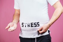 Stress, mind problems, compulsive overeating. Stress, mind problems, bulimia, compulsive overeating, weight gain. overweight man with pills and measuring tape stock photo