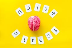 Stress and noise text with brain for psychological health in office concept on yellow background top view.  stock photo