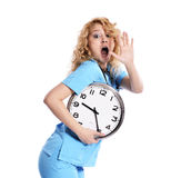 Stress - nurse woman running late. With clock under her arm. Healthcare concept photo with young worker in a hurry running against time. Caucasian model Royalty Free Stock Image