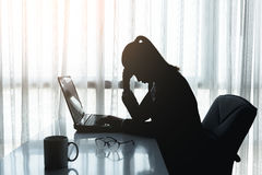 Stress in the office. Businesswoman using computer in the office. Stress in the office. Silhouette Colour Tone Stock Images