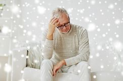 Senior man suffering from headache at home. Stress, old age and people concept - senior man suffering from headache at home over snow Royalty Free Stock Photo