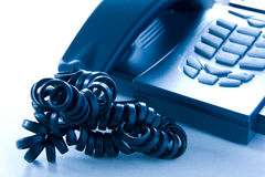 Stress phone. An office phone with a curled up cord, shot in tungsten light. Focus on the cord Stock Image