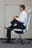 Stress reduction in office work - man exercising on chair Stock Photography