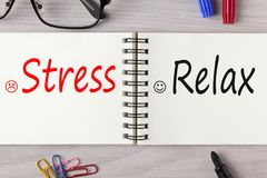 Stress or Relax written on notebook concept. Stress or Relax written on notebook on wooden desk with marker pen and glasses. Business concept Stock Photo