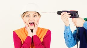 Stress resistance concept. Lady stressful and shocked. Male hands with drill drills head of woman, white background. Woman with scared face in helmet, hard hat stock photos