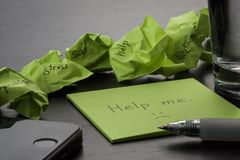 Depression. The phrase `help me` is written on a green sticky note on wooden black table. Crumpled green sticky notes are scattere royalty free stock photos