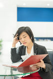 Stress Thai (Asian) businesswoman is reading her document file i Royalty Free Stock Photography