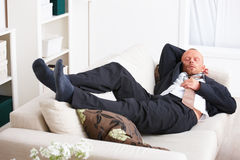 Stress -  Tired business man sleeping on a sofa Stock Images