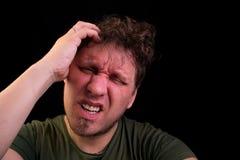 stress Um homem guarda sua cabeça com suas mãos O homem sente uma dor de cabeça foto de stock royalty free